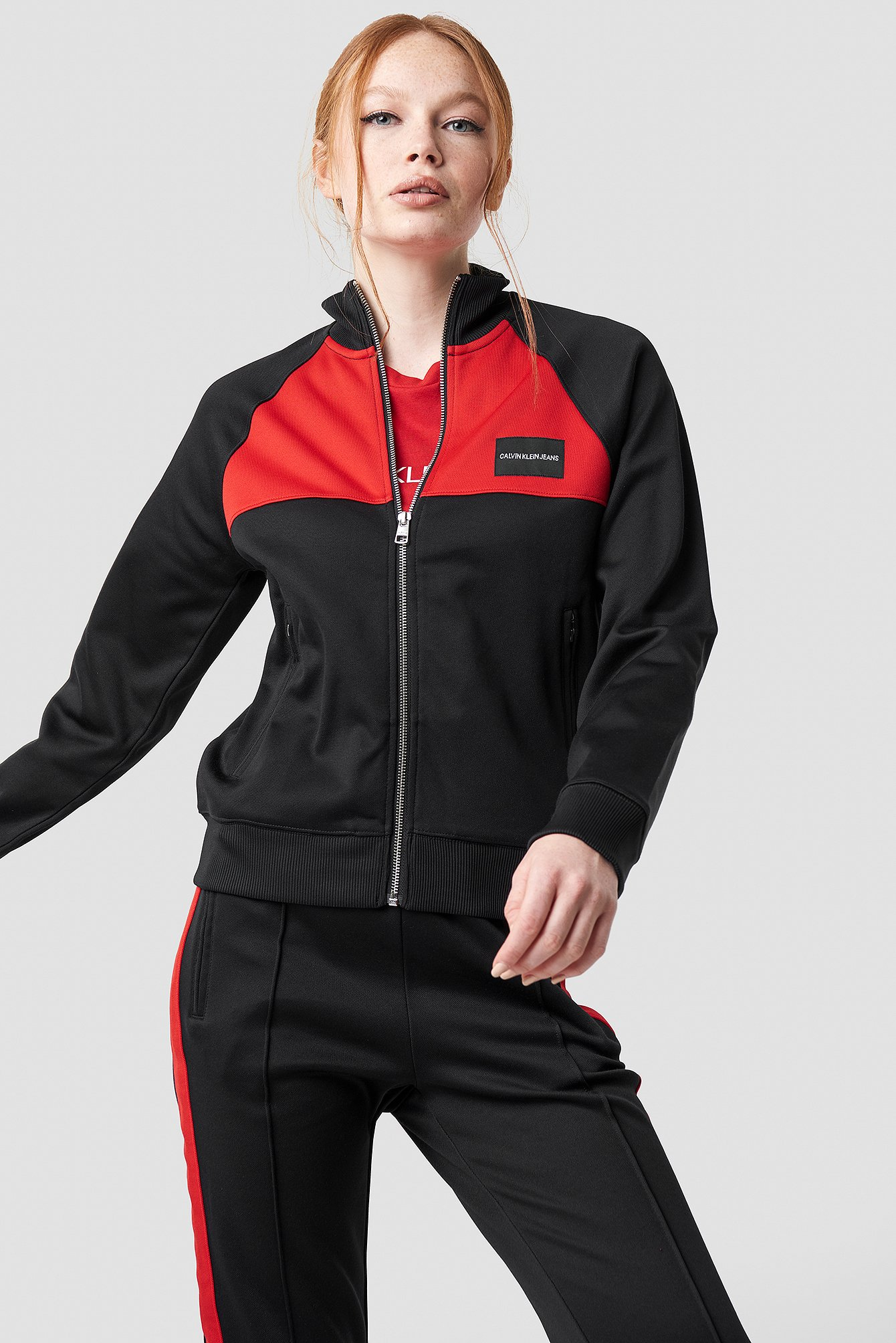 This tracksuit jacket by Calvin Klein features a ribbed high neck, a center zipper down the front, side pockets and a ribbed elasticized waist and cuff.