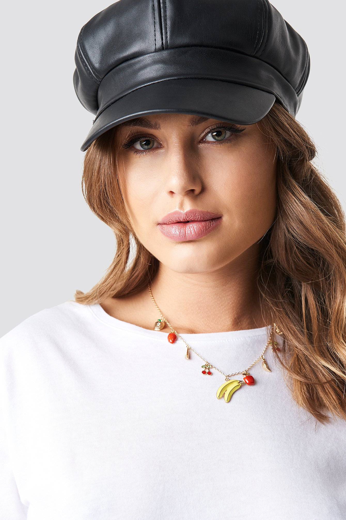 The Mixed Fruits Necklace by NA-KD Accessories features a thin chain, an adjustable clasp closure, and one big banana pendant, surrounded by various smaller fruit pendants.