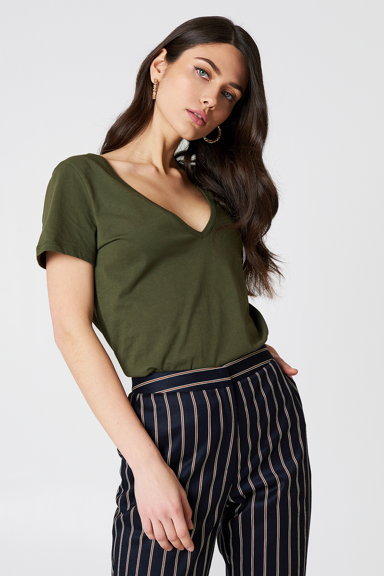 The V-neck Tee by NA-KD Basic features a v-neckline, short sleeves, and a relaxed fit.