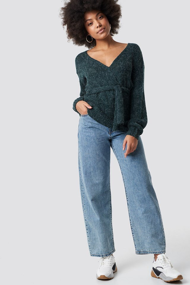 Green V-Neck Knitted Sweater with Wide Jeans and White Sneakers.