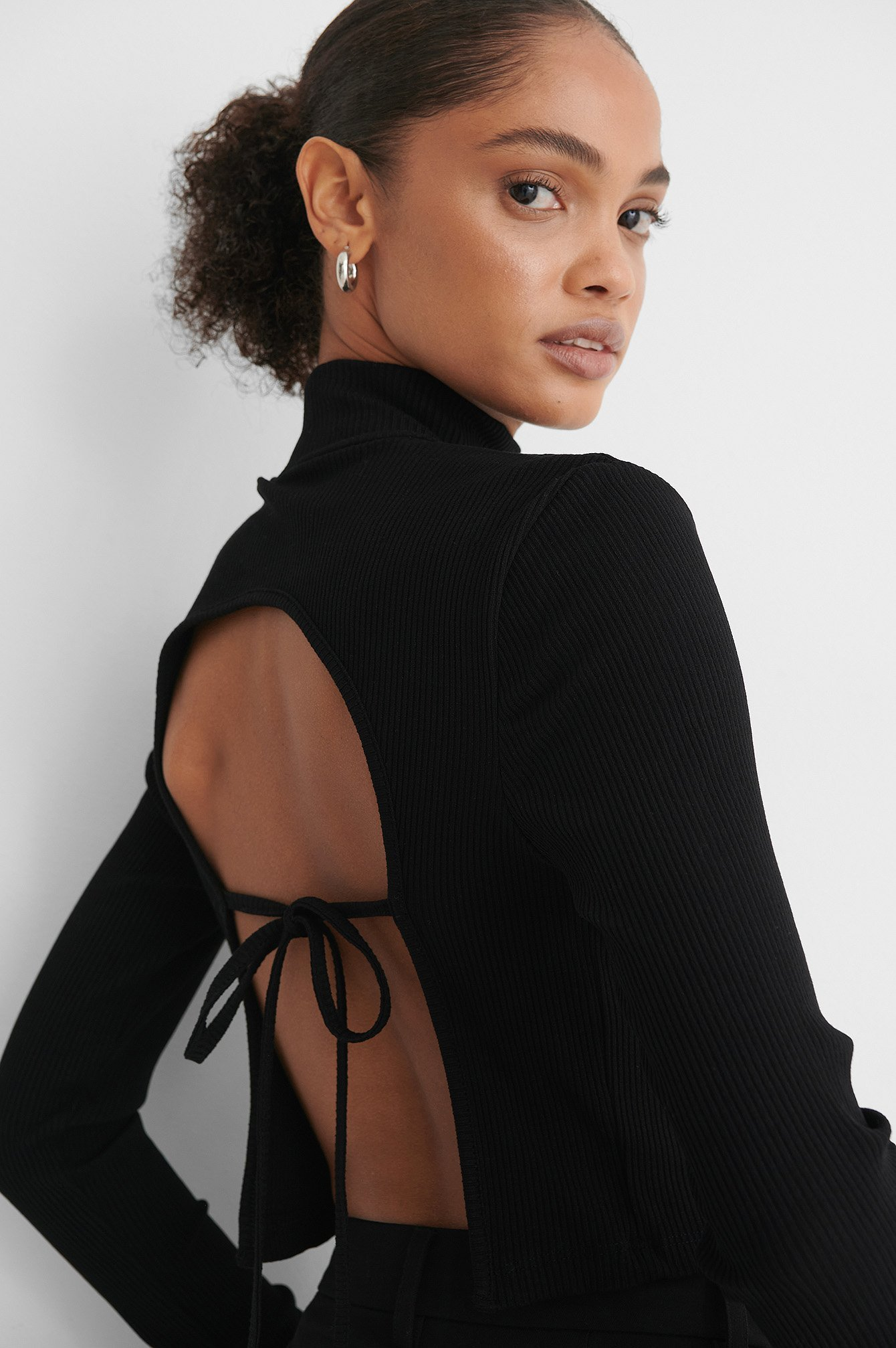 Woman wears Black Open Back top with Knot Detail and looks at camera