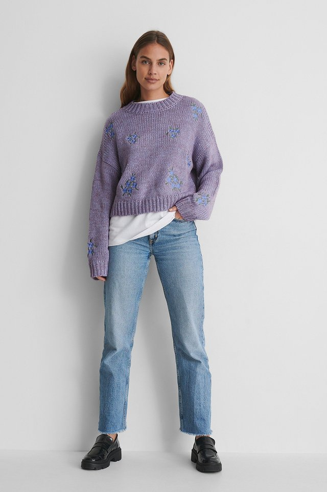 Flower Embroidery Round Neck Knitted Sweater with a White T-shirt and Jeans.