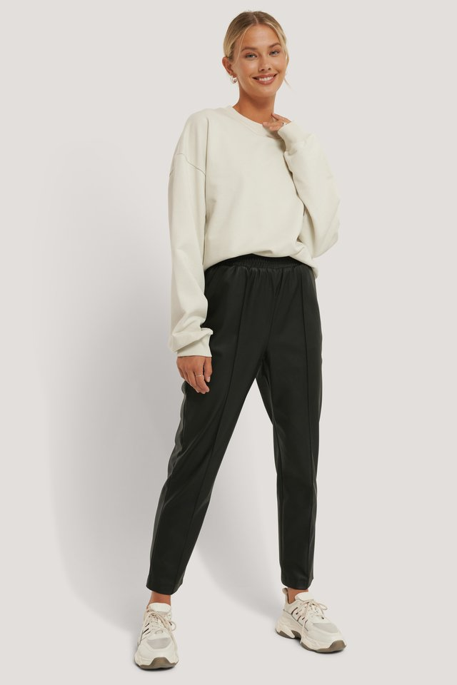 Recycled Elastic Waist PU Pants with a Beige Sweater.