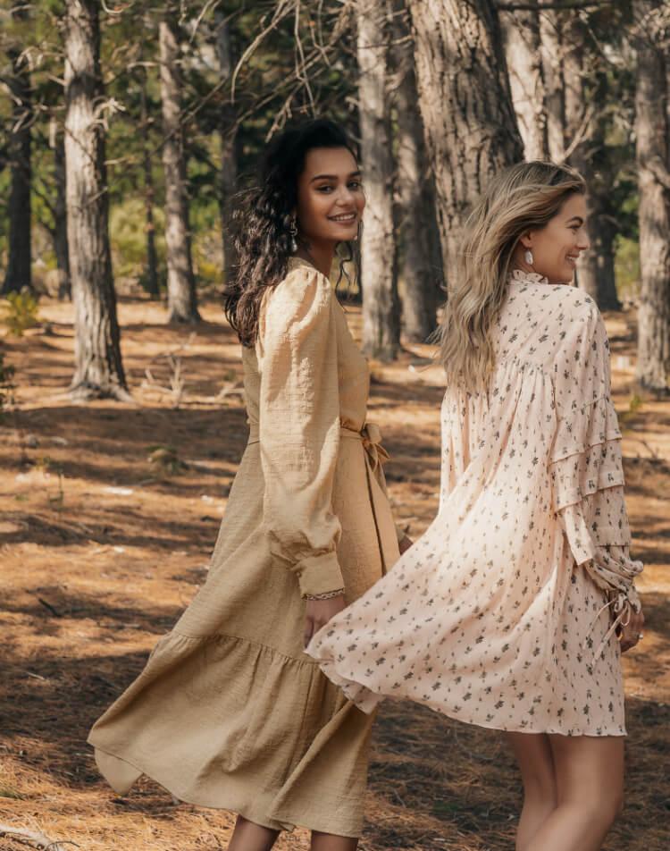 Two girls wearing dresses in dusky light